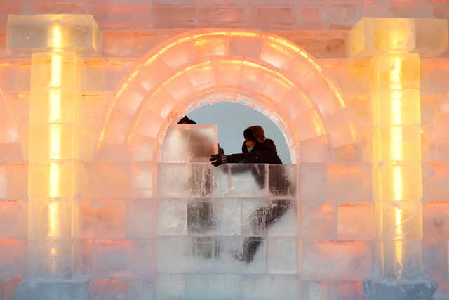 Workers place an ice block onto an ice structure at the site of the Harbin International Ice and Snow Festival before its opening in Harbin, China, December 16, 2020. REUTERS/Carlos Garcia Rawlins