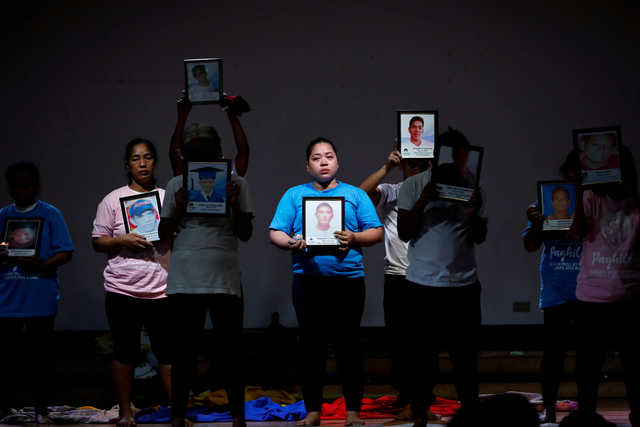 Bereaved relatives of Philippines' drug war victims hold portraits of their slain loved ones during their theatre performance depicting their journey of loss and healing in a Catholic school in Makati City. REUTERS/Eloisa Lopez