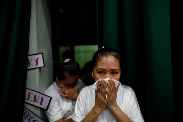A bereaved mother and a widow of Philippines' drug war victims are seen emotional as they prepare for the theatre performance on their journey of loss and healing in a Catholic school in Makati City. REUTERS/Eloisa Lopez