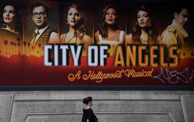 A woman wearing a protective face mask walks past a billboard outside of the Garrick Theatre promoting the West End musical 'City of Angels', following the outbreak of the coronavirus disease, in London, Britain. REUTERS/Toby Melville